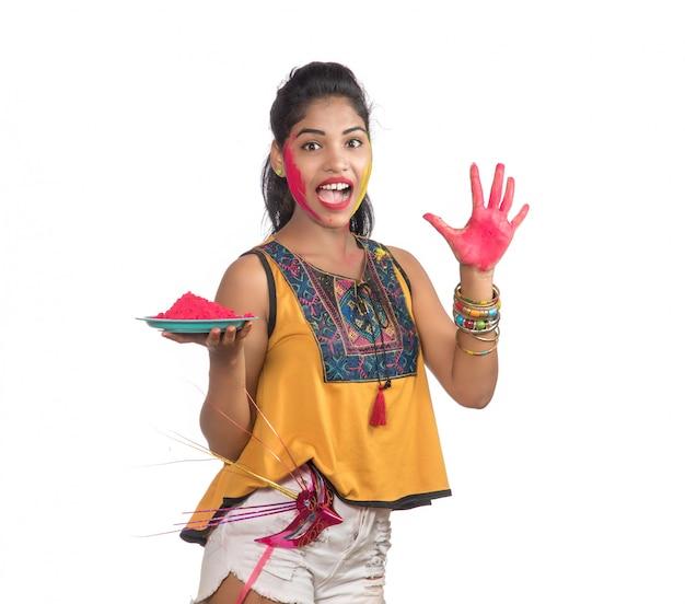 Mooi jong meisje met gepoederde kleur in plaat met carnaval masker ter gelegenheid van holi festival. Premium Foto