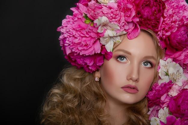 Mooi jong meisje met pioenrozen Premium Foto