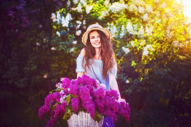 Mooi jong meisje met uitstekende fiets en bloemen op stad backgroundd in het zonlicht openlucht. Premium Foto