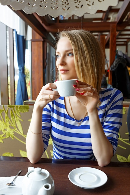 Mooi jong meisje rusten in een café en keek uit het raam Premium Foto