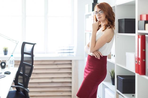 Mooi jong meisje staat in het kantoor in de buurt van een plank met documenten. Premium Foto