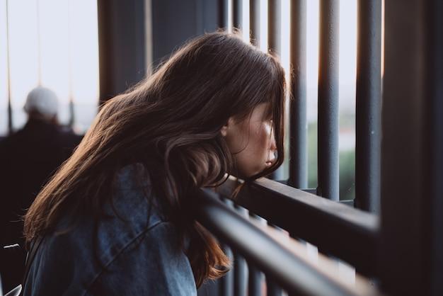 Mooi jong meisjesportret achter een ijzeromheining Gratis Foto
