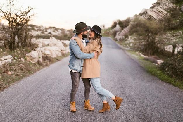 Mooi jong paar dat op een weg loopt Gratis Foto