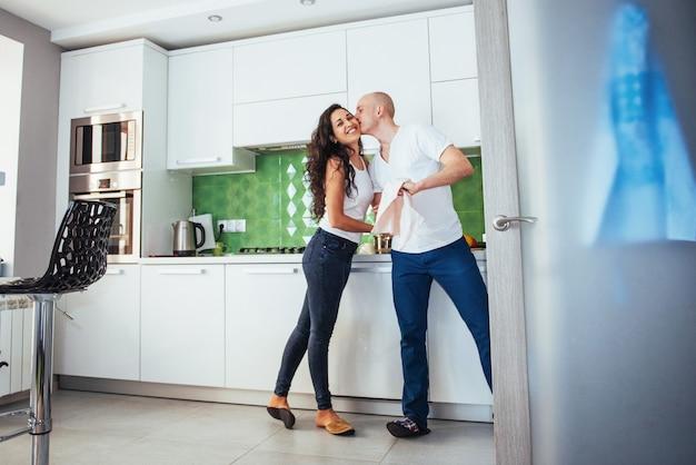 Mooi jong paar ik praten, kijken en glimlachen tijdens het koken in de keuken. Premium Foto
