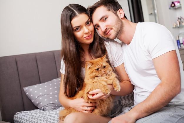Mooi jong paar op bed het spelen met een rode kat Premium Foto