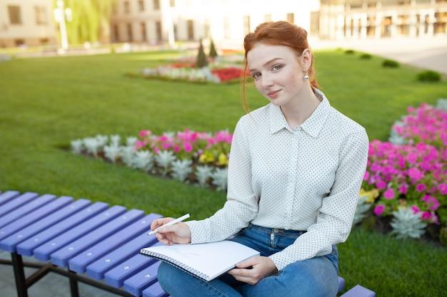 Mooi jong roodharig meisje met sproeten die op een bank zitten Premium Foto