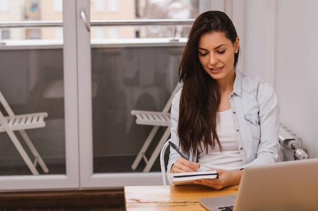 Mooi jong student het schrijven thuiswerk die laptop en boek met behulp van Premium Foto