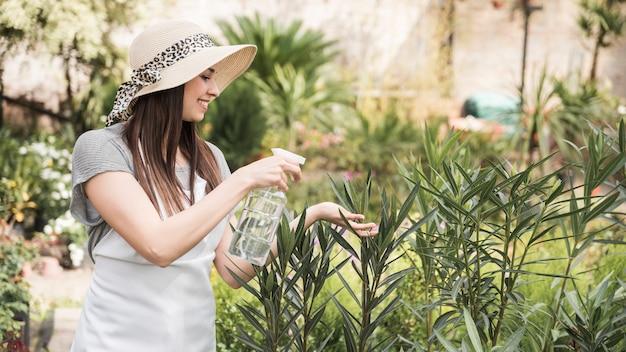 Mooi jong vrouwen bespuitend water van fles bij het kweken van installaties Gratis Foto