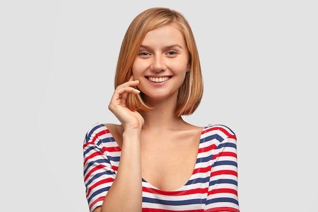Mooi jong vrouwenmodel met zachte glimlach, kort haar en sproetenhuid, houdt hand dichtbij gezicht Gratis Foto