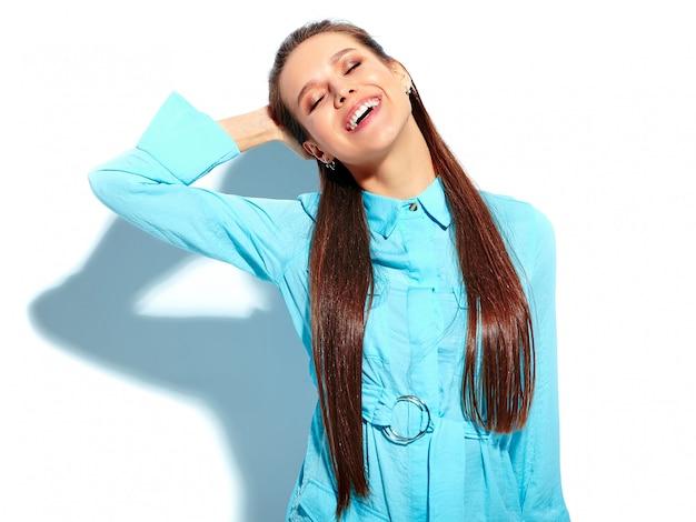 Mooi kaukasisch het glimlachen donkerbruin vrouwenmodel in heldere blauwe de zomer modieuze die kleding op witte achtergrond wordt geïsoleerd Gratis Foto