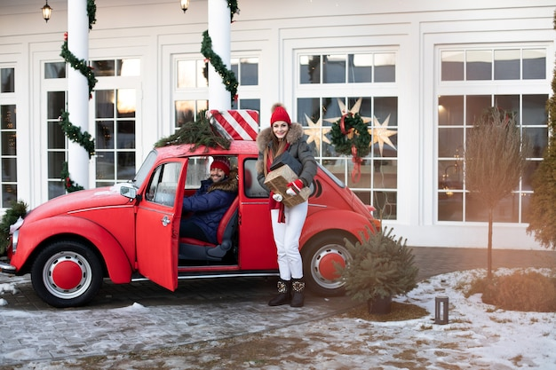 Mooi kaukasisch meisje in warme winterkleren draagt dozen met kerstcadeaus in een rode auto naar haar man Gratis Foto