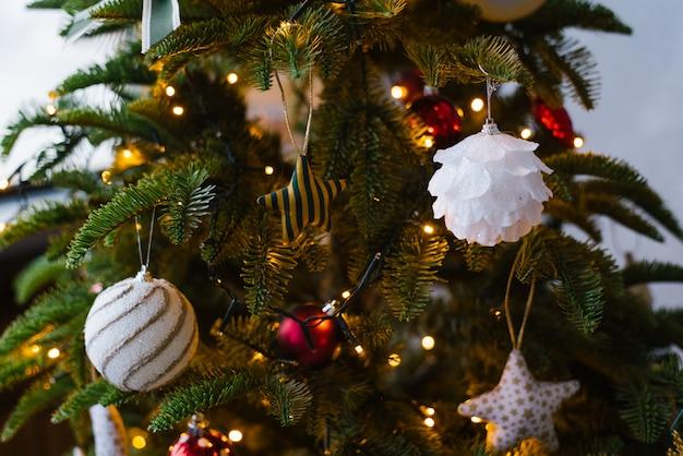 Mooi kerstboomspeelgoed op kerstboom met lichten Premium Foto