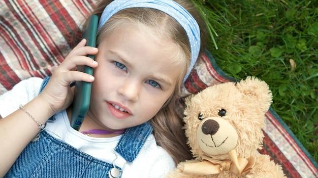 Mooi kindmeisje dat op een deken op groen gazon in de zomer met haar teddybeerstuk speelgoed spreekt op mobiele telefoon. Premium Foto