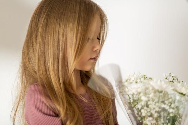 Mooi klein blond meisje met lang haar met een boeket bloemen Premium Foto