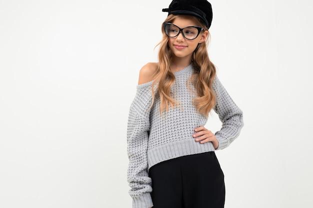 Mooi klein meisje in grijze blouse, pet en glazen glimlacht geïsoleerd Premium Foto
