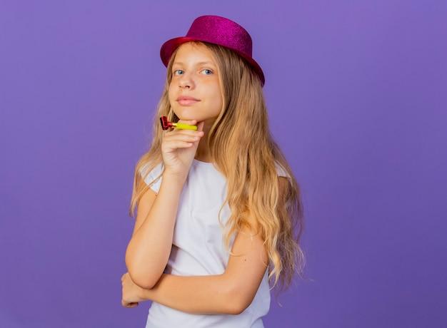 Mooi klein meisje in vakantie hoed bedrijf fluitje kijken camera lachend met blij gezicht, verjaardagsfeestje concept permanent over paarse achtergrond Gratis Foto
