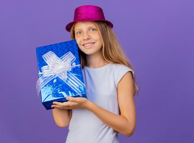 Mooi klein meisje in vakantie hoed houden geschenkdoos camera kijken met blij gezicht glimlachen, verjaardagsfeestje concept permanent over paarse achtergrond Gratis Foto