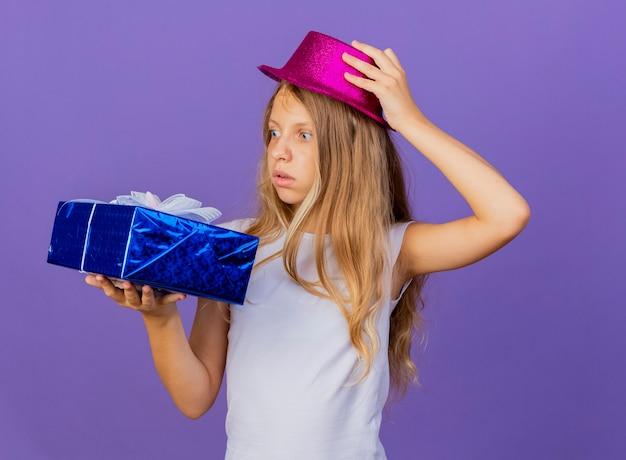Mooi klein meisje in vakantie hoed houden geschenkdoos kijken naar het wordt geïntrigeerd, verjaardagsfeestje concept staande over paarse achtergrond Gratis Foto