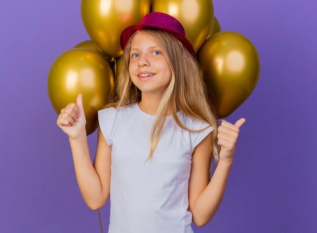 Mooi klein meisje in vakantie hoed met bos van baloons kijken camera glimlachen duimen opdagen, verjaardag partij concept staande over paarse achtergrond Gratis Foto