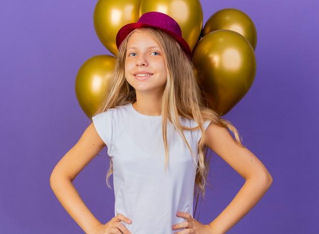 Mooi klein meisje in vakantie hoed met bos van baloons kijken camera glimlachend vrolijk, verjaardagsfeestje concept staande over paarse achtergrond Gratis Foto