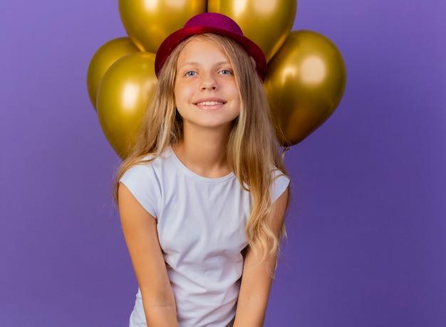 Mooi klein meisje in vakantie hoed met bos van baloons lookin camera glimlachen vrolijk blij en positief, verjaardagsfeestje concept staande over paarse achtergrond Gratis Foto