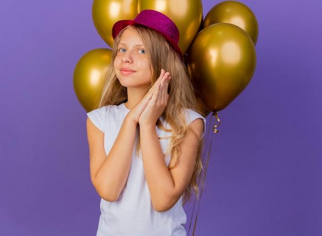 Mooi klein meisje in vakantie hoed met bos van baloons palmen bij elkaar te houden glimlachend wachten op verrassing, verjaardagsfeestje concept permanent over paarse achtergrond Gratis Foto