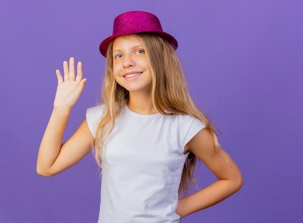 Mooi klein meisje in vakantie hoed zwaaien met hand blij en positief, verjaardagsfeestje concept permanent over paarse achtergrond Gratis Foto