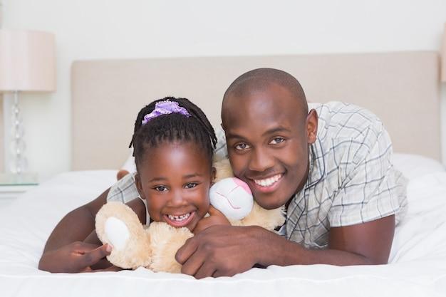Mooi klein meisje met zijn vader in bed thuis in de slaapkamer