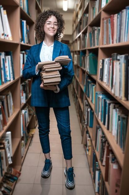 Mooi krullend meisje in glazen en een blauw pak staat in de bibliotheek Premium Foto
