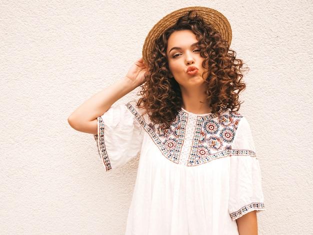 Mooi lachende model met afro krullen kapsel gekleed in zomer hipster witte jurk. Gratis Foto