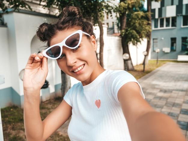 Mooi lachende model met hoorns kapsel gekleed in zomer casual kleding. sexy zorgeloos meisje poseren in de straat in zonnebril. selfie zelfportret foto's maken op smartphone Gratis Foto