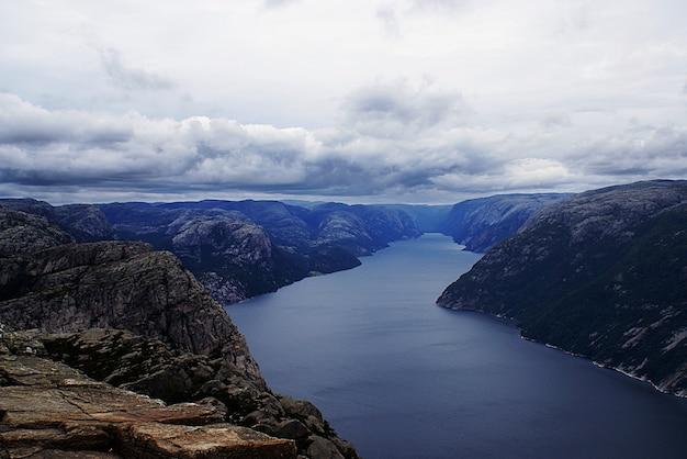 Mooi landschap van beroemde kliffen preikestolen in de buurt van een meer onder een bewolkte hemel in stavanger, noorwegen Gratis Foto