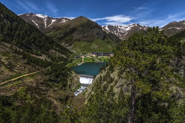 Mooi landschap van de vallei van núria in spanje, het hotel en zijn dam vóór de pyreneeën Premium Foto