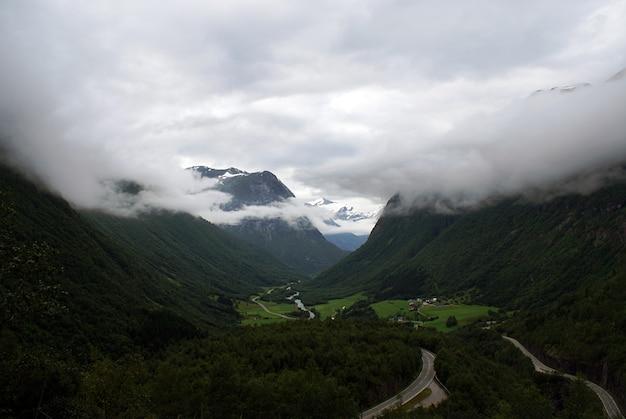 Mooi landschap van een groen landschap van bergen gehuld in mist Gratis Foto