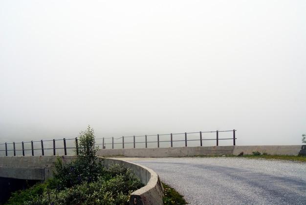 Mooi landschap van een weg op een sombere dag met een mistige achtergrond in noorwegen Gratis Foto