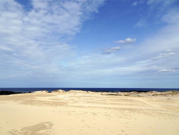 Mooi landschap van een zandstrand onder een bewolkte hemel in leba, polen Gratis Foto