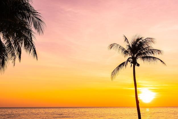 Mooi landschap van overzeese oceaan met de palmboom van de silhouetkokosnoot bij zonsondergang of zonsopgang Gratis Foto