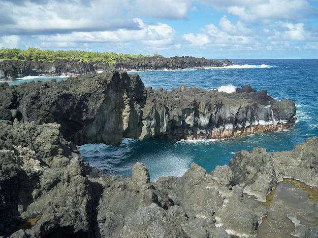 Mooi landschap van scherpe rotsformaties op het strand onder de bewolkte hemel in hawaï Gratis Foto