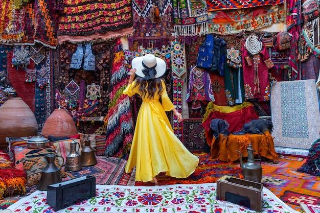 Mooi meisje bij traditionele tapijtwinkel in de stad van goreme, cappadocië in turkije. Gratis Foto
