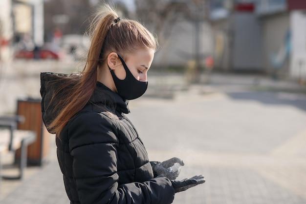 Mooi meisje blijft achter de tafel met gezichtsmasker tegen covid-19, coronavirus, spuit desinfectievloeistof op chirurgische handschoenen en wacht op passagiers op de luchthaven van belgrado Premium Foto