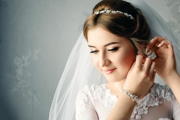 Mooi meisje, bruid in een witte jurk op de achtergrond van het appartement. bruiloft, bruidspaar, familiecreatie. Premium Foto