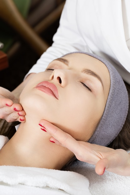 Mooi meisje dat gezichtsmassage doet bij de kuuroordsalon Premium Foto