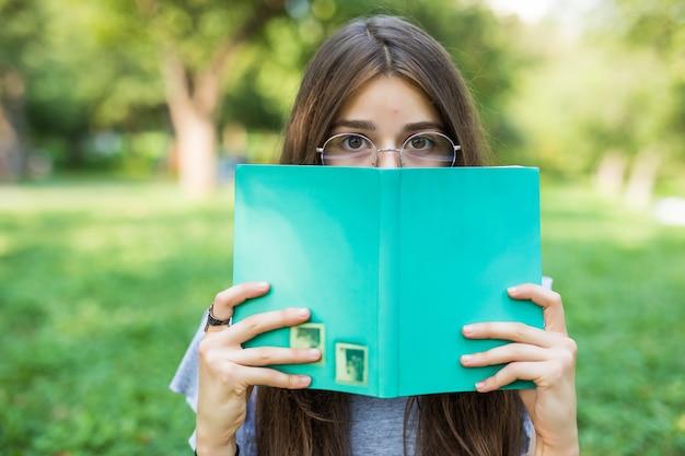 Mooi meisje dat haar gezicht behandelt met boekonderwijs en de selectieve nadruk van het mensenconcept. Gratis Foto