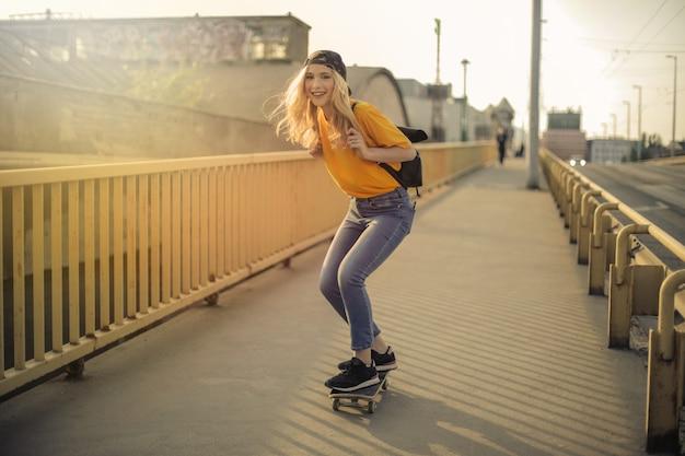 Mooi meisje dat in de stad met een skateboard rijdt Premium Foto