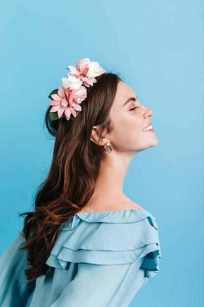 Mooi meisje dat oprecht op geïsoleerde muur glimlacht. model in kroon van bloemen poseren voor portret in profiel. Gratis Foto