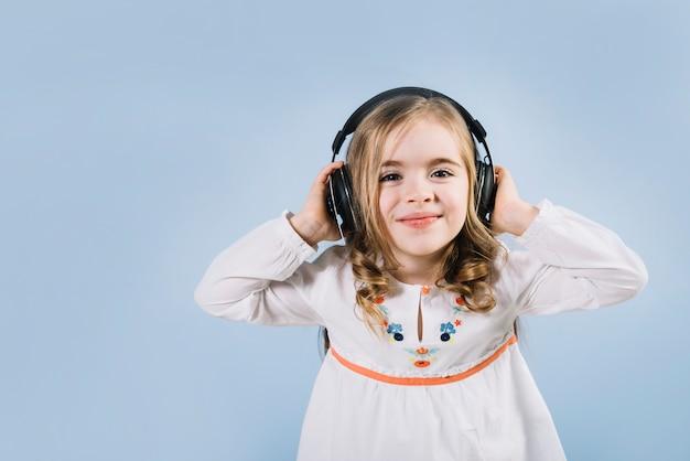 Mooi meisje dat van de muziek op hoofdtelefoon tegen blauwe achtergrond geniet Gratis Foto