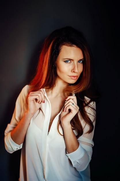 Mooi meisje dat zich dichtbij de donkerblauwe muur in duisternis bevindt Premium Foto