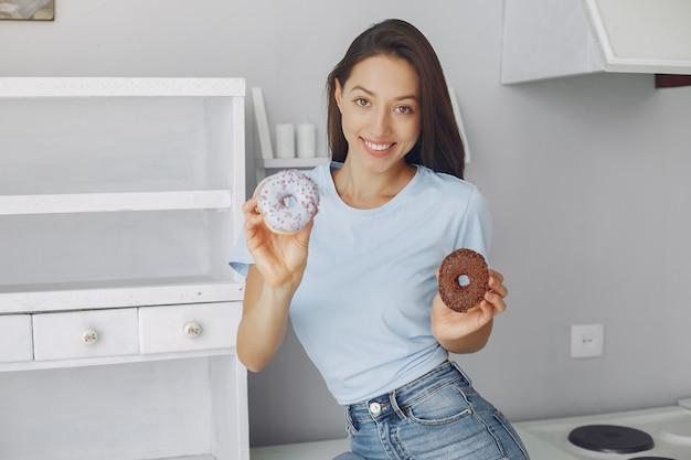 Mooi meisje dat zich in een keuken met doughnut bevindt Gratis Foto