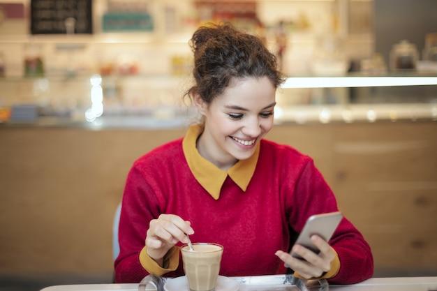 Mooi meisje die haar smartphone in een café controleren Premium Foto