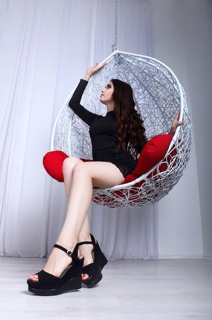 Mooi meisje en decoratieve schommel Premium Foto
